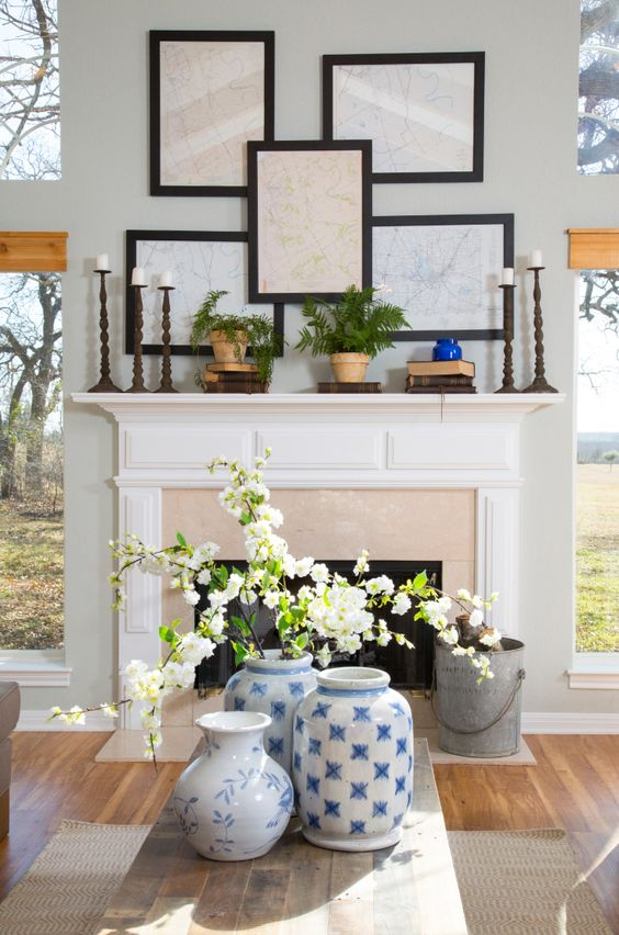 White flowers in oriental vases sit on the coffee tablem and maps of the county where the Mahans live which were found in the closet have been framed and hung as an art piece above the mantle, as seen on HGTV's Fixer Upper. (detail)